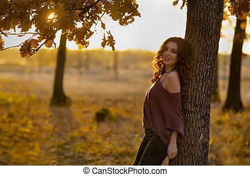 A portrait of a beautiful young woman in an autumn forest. Lifes