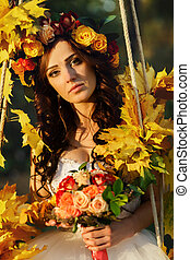 A portrait of a bride sitting on the swing decorated with golden autumn leaves