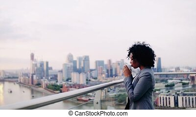 A portrait of a businesswoman standing on a terrace, drinking coffee.