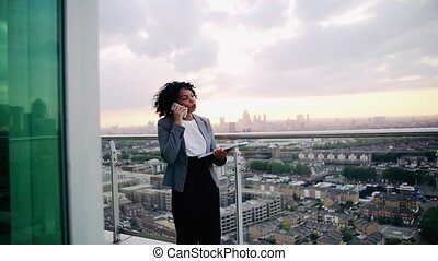A portrait of a businesswoman standing on a terrace, making...