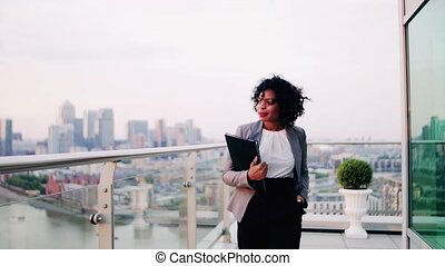 A portrait of a businesswoman walking on a terrace at...