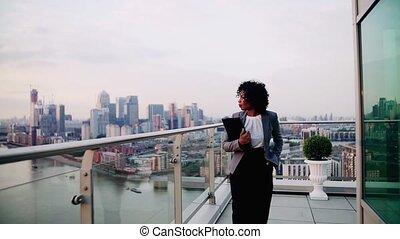 A portrait of a businesswoman walking on a terrace in the...