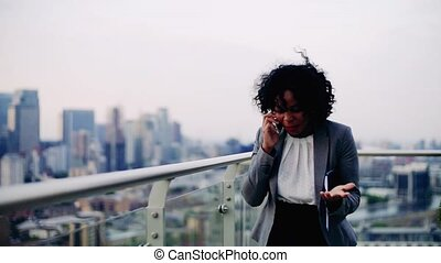 A portrait of a businesswoman walking on a terrace, making a...