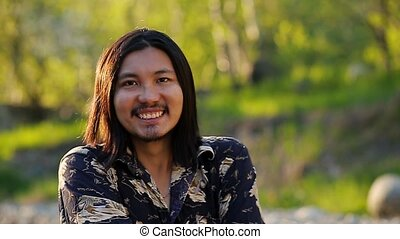 A portrait of a cheerful asian guy smiling to the camera against a beautiful sunset background in the mountains