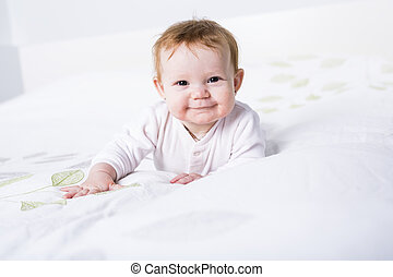 Portrait of a crawling baby on the bed in her room