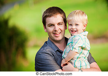 A portrait of a Dad and his little boy taken outdoors in a green field.