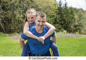 portrait of a father carrying teen girl on back at the park
