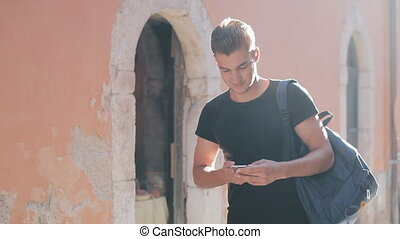 A portrait of a handsome young man surfing smartphone and...