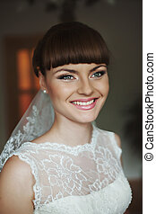 A portrait of a smiling bride with tender pink lips