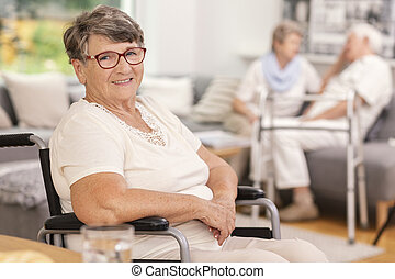 A portrait of a smiling elderly woman in a wheelchair inside a common room of a luxurious care home for seniors. Blurred background.