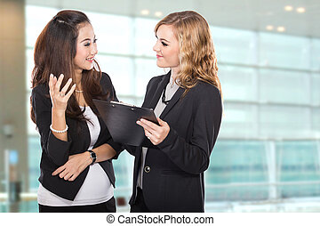 A portrait of a two young businesswoman wtih a clipboard discussing