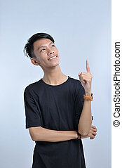 A portrait of a young asian man getting an idea hand gesture. pointing up to copy space. pointing with the index finger a great idea