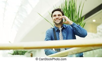 A portrait of a young businessman with smartphone standing inside a building.