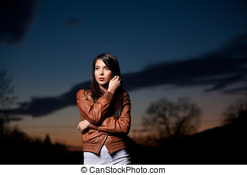 a portrait of a young woman at sunset