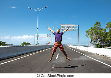 Asian Man jump on the empty highway