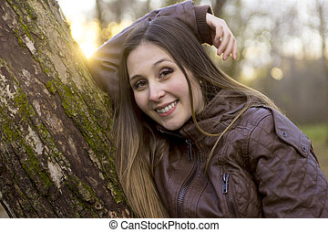Portrait of beautiful young brunette girl in the park at fall.