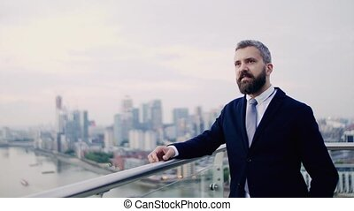 A portrait of businessman standing against London view...