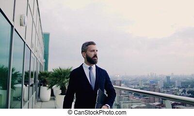A portrait of businessman walking on a terrace against...