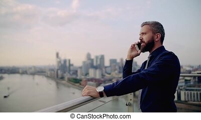 A portrait of businessman with smartphone standing against...