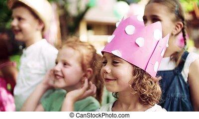 A portrait of children standing on birthday party in garden ...