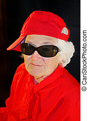 a portrait of elderly woman in red and in antisun glasses