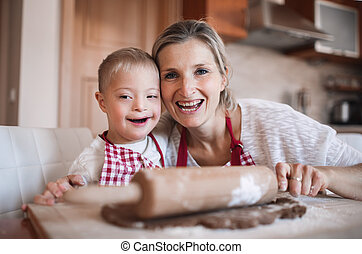 A portrait of handicapped down syndrome boy with his mother indoors baking.