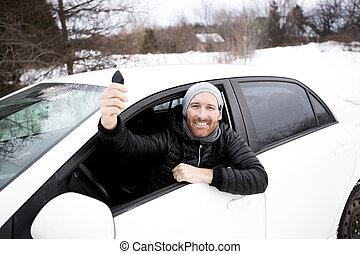 Portrait of handsome man in car in winter