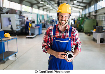 A portrait of handsome metal industry worker in factory