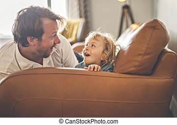 Portrait of happy son with father at home