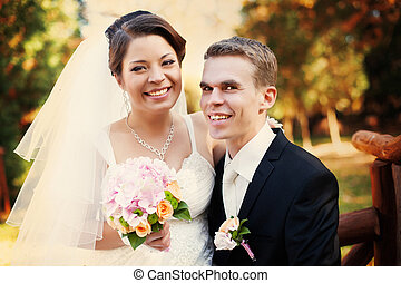 A portrait of happy wedding couple sitting on the bench in an autumn park