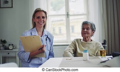 A portrait of health visitor and a senior woman in...