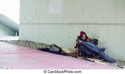 A portrait of homeless beggar man lying down outdoors. - A...