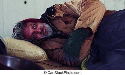 A portrait of homeless beggar man lying outdoors. - A...
