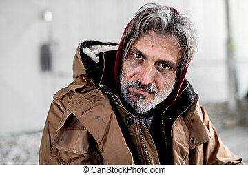 A portrait of homeless beggar man sitting outdoors.