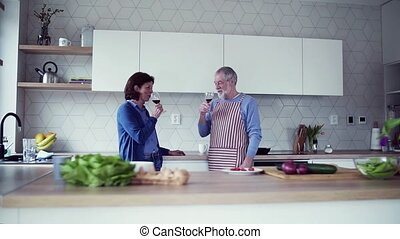 A portrait of senior couple in kitchen indoors at home,...
