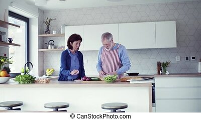 A portrait of senior couple in love indoors at home,...