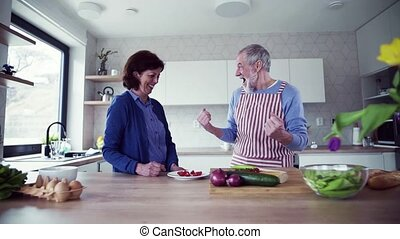 A portrait of senior couple in love indoors at home, preparing food.