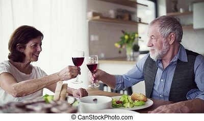 A portrait of senior couple indoors at home, clinking...
