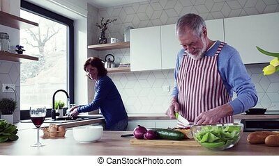 A portrait of senior couple indoors at home, cooking. Slow...