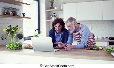 A portrait of senior couple with laptop indoors at home, cooking.