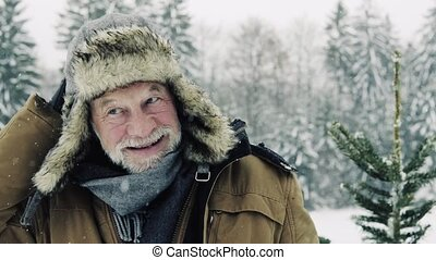 A portrait of senior man in forest on snowy winter day.