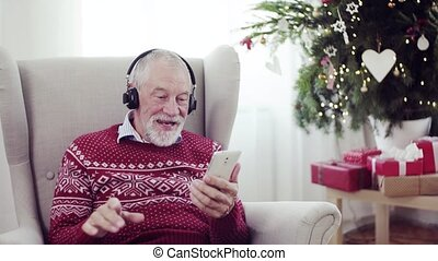 A portrait of senior man with headphones sitting on armchair at home at Christmas time.