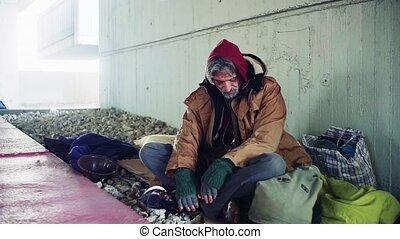 A portrait of tired homeless beggar man sitting outdoors....