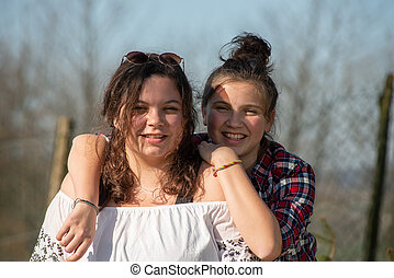 portrait of two happy sisters, outdoors