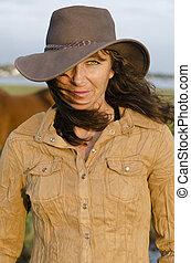A portrait of woman wearing western hat.