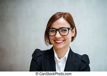 A portrait of young businesswoman standing in office, looking at camera.