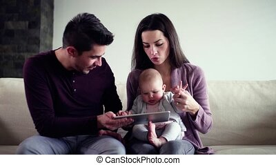 A portrait of young couple sitting on a sofa, entertaining baby with tablet.