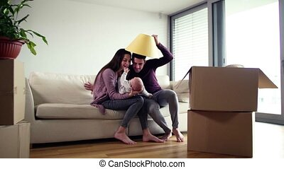 A portrait of young couple with a baby and cardboard boxes moving in a new home.