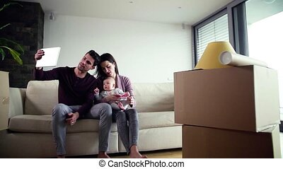 A portrait of young couple with a baby and tablet moving in a new home.