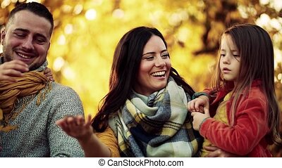 A portrait of young family with two small children in autumn...